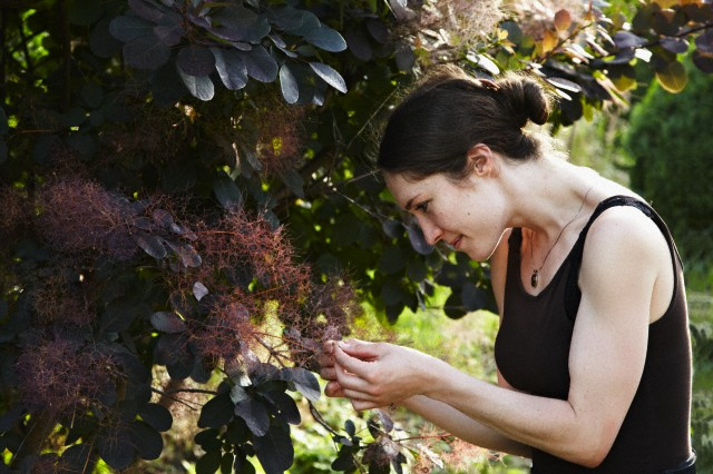 young adult woman examine a bloom of an exotic plant